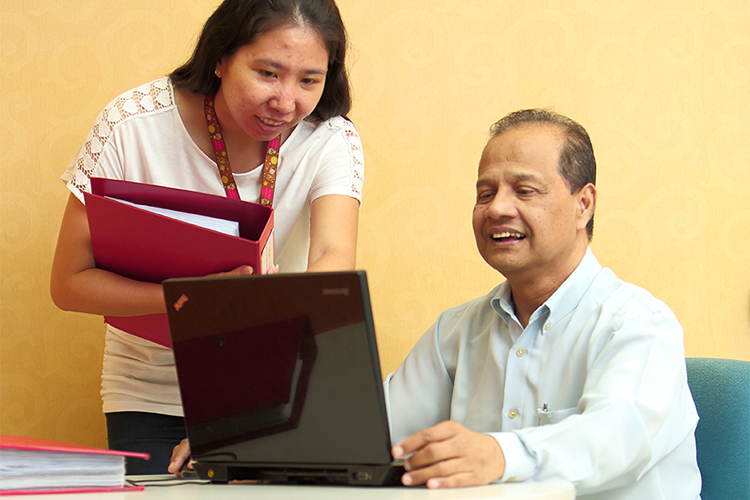 Business professional male and female colleagues reviewing a report on a tablet